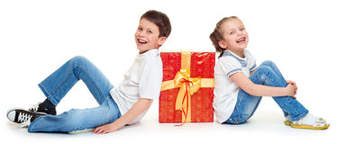 Boy and girl with red gift box and golden bow - holiday object concept isolated Royalty Free Stock Photo