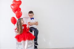 Boy and girl with red heart-shaped balloons on birthday party