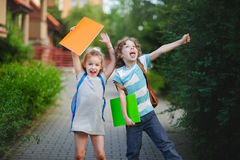 Boy and girl rejoice to the termination of academic year. They have raised hands and pose ridiculous mugs. Behind the back of everyone satchel Stock Image