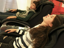 Boy in girl relaxing in massage chair Stock Image