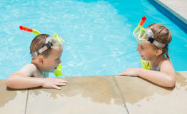 Boy and girl relaxing on the side of swimming pool Royalty Free Stock Image