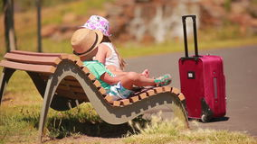 Boy and girl resting on a bench after a long road. With a suitcase stock video footage