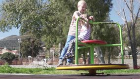 A boy and a girl ride in the park on a swing.  stock footage