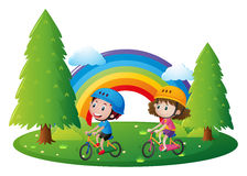 Boy and girl riding bicycle in park Stock Photos