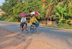 Boy and girl riding bicycle. Laos. Stock Photo