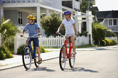 Boy and Girl Riding Bikes. Brother and sister riding bikes together on street.  Horizontally framed shot Stock Image