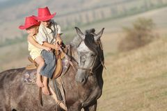 Boy and girl riding a horse on farm Stock Photos