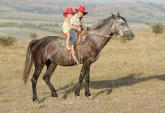Boy and girl riding a horse on farm Royalty Free Stock Images