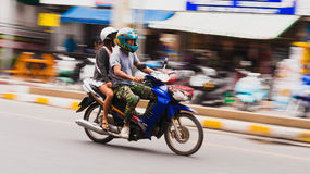 A boy and  girl riding on a motorcycle.Blurred motion Stock Images
