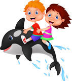 Boy and girl riding orca Royalty Free Stock Image