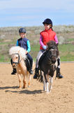 Boy and girl riding  ponies Stock Photography