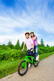 Boy and girl riding same bike that both stand Royalty Free Stock Photography