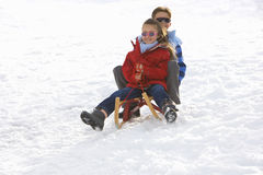 Boy and girl (7-9) riding sled down snow slope, smiling, low angle view Royalty Free Stock Image