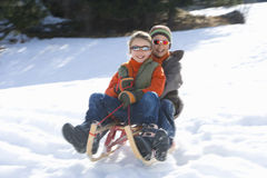 Boy and girl (7-9) riding sled down snow slope, wearing sunlgasses, smiling, low angle view Stock Image