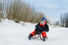 Boy and girl are riding on sleds royalty free stock photos
