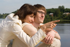 Boy and girl on the river`s bank Stock Images