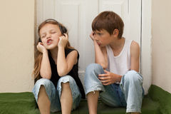 A boy,a girl,and rock and roll. Annoyed little boy listening to his sister singing stock photos