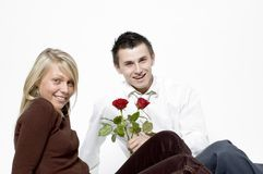 Boy and girl / roses. Boy and girl sitting down - boy holding 2 red roses Royalty Free Stock Photography