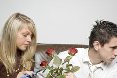Boy & girl / roses. Boy is holding three red roses and looking away while girl beside him puts scissors to one of the roses. (Boy in relaxed office attire Stock Photo