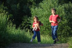 Boy and girl run with doll in park Stock Photo
