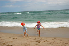 Boy and girl runing from ocean surf Stock Photography