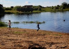 A boy and a girl are running along the bank of the Klyazma river. Vladimir region. Russia. stock photography
