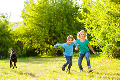 Boy and a girl running away from dog or doberman Royalty Free Stock Photo