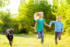 Boy and a girl running away from dog or doberman Stock Photography