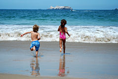 Boy and girl running on beach Stock Images