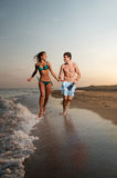 Boy and girl running on beach. Young boy and girl running on beach Stock Photo