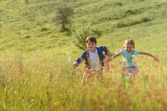 Boy and girl running on field Stock Photos