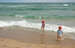Boy and girl running from ocean surf royalty free stock photos