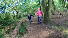 Children running in forest. Boy and girl running quickly on a narrow path in a forest in summer stock video footage