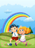 A boy and a girl running with a rainbow in the sky Royalty Free Stock Image