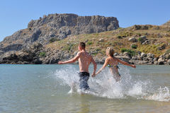A boy and girl running into the sea Royalty Free Stock Photography