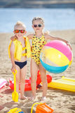 Boy and girl on a sandy beach with a large inflatable ball. Little girl with pigtails and a little blonde boy with short hair, a brother and sister, both wearing Royalty Free Stock Photography
