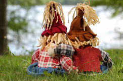 Boy and girl scarecrows back view sitting by lake. Boy and girl scarecrows back view sitting in grass by lake Stock Photography