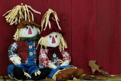 Boy and girl scarecrows sitting by antique red wooden barn Royalty Free Stock Image