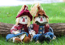 Boy and girl scarecrows sitting on grass by log next to a lake Royalty Free Stock Photography