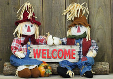 Boy and girl scarecrows sitting on log holding red wood welcome sign. Boy and girl scarecrows sitting on log by pumpkin holding red wood welcome sign Royalty Free Stock Photo