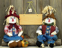 Boy and girl scarecrows sitting on log by pumpkin and blank wood sign Royalty Free Stock Photos