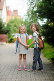Boy and girl with schoolbags hold hands. Stock Image