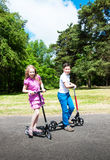 Boy and girl on scooters Royalty Free Stock Images