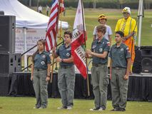 Boy and Girl Scouts Hold the American Flag during the National Anthem at the Annual Rubber Duck Festival. All stand at attention during the singing of the royalty free stock photo