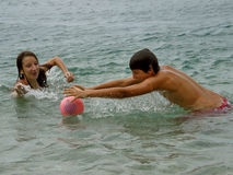 Boy and girl in sea. Young boy and girl (best friends) in the fight for the ball on sea. They are spending summer holidays and playing water polo in Adriatic sea Royalty Free Stock Photography