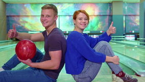 Boy and girl show their thumbs up at the bowling stock video