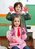Boy And Girl Showing Colored Hands In Classroom Stock Image