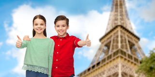 Boy and girl showing thumbs up over eiffel tower Stock Image