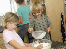 Boy (5-7) and girl (6-8) sieving flour into bowl, smiling, mother standing at kitchen sink (tilt) Royalty Free Stock Photos