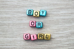 Boy or girl sign. BOY OR GIRL cube blocks arranged on gray wooden background Royalty Free Stock Photography
